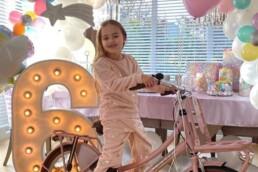 lichtletter cijfer 6 met een meisje op een fiets