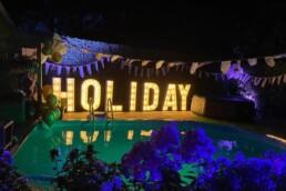 lichtletters in het woord holiday met lampjes
